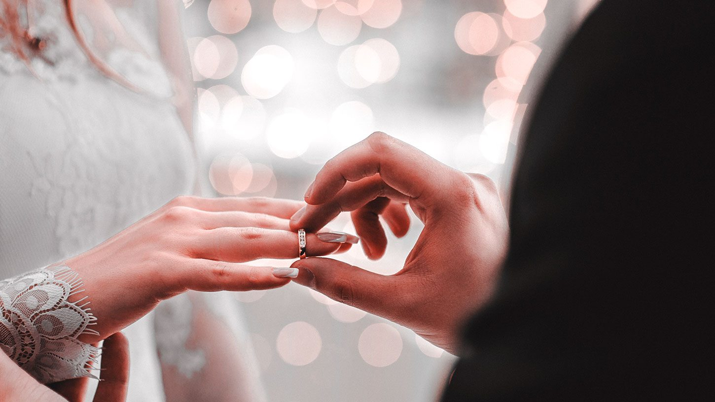Groom placing wedding ring on Brides hand