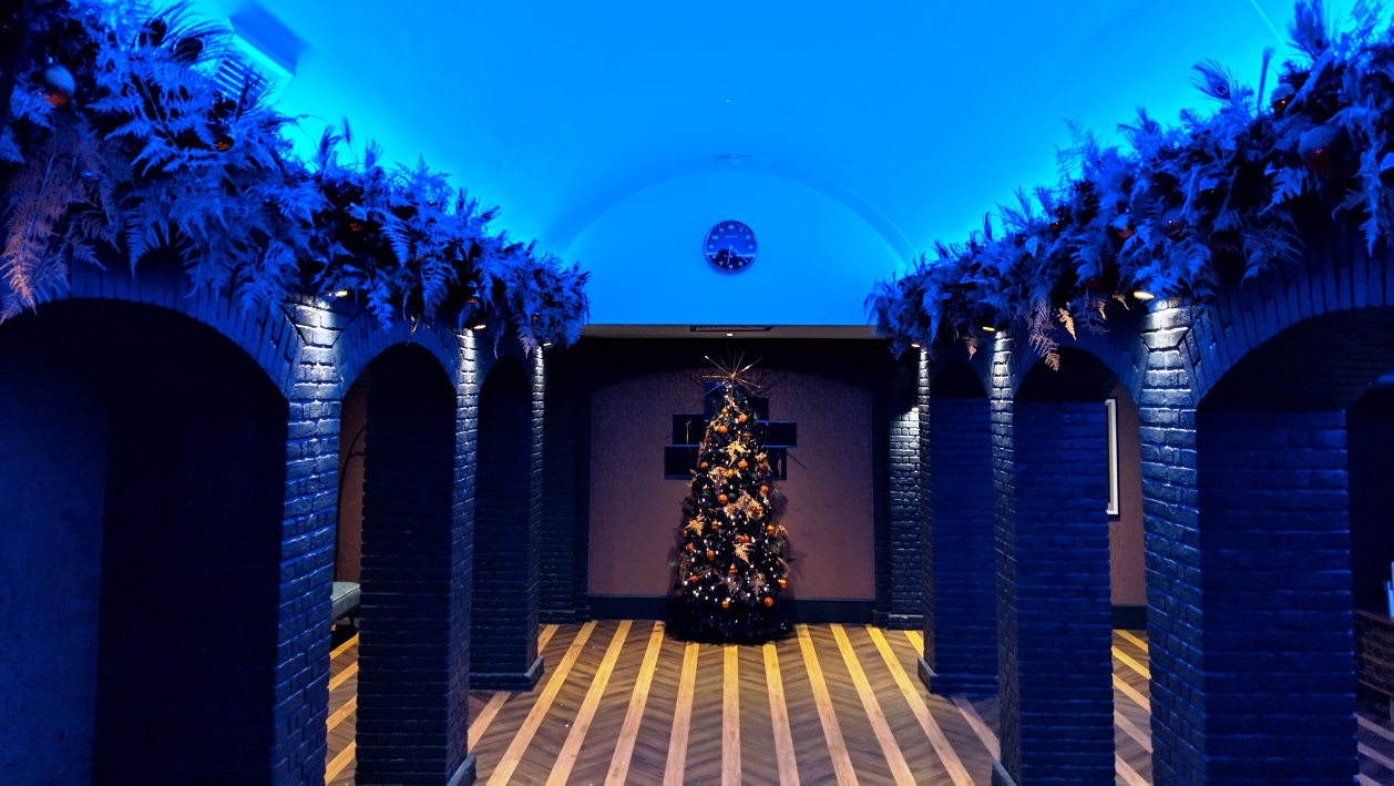 Decorated Christmas tree in a blue lit room at Grubstreet Author